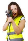 La muchacha en un chaleco de la construcción un taladro eléctrico Fotografía de archivo
