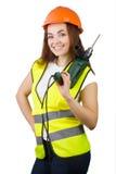 La muchacha en un chaleco de la construcción y un casco con un taladro eléctrico Foto de archivo
