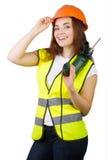 La muchacha en un chaleco de la construcción y un casco con un taladro eléctrico Imagenes de archivo