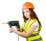 La muchacha en un chaleco de la construcción y un casco con un taladro eléctrico Fotos de archivo