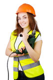 La muchacha en un chaleco de la construcción y un casco con un taladro eléctrico Fotos de archivo libres de regalías