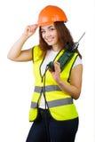 La muchacha en un chaleco de la construcción y un casco con un taladro eléctrico Imagen de archivo libre de regalías
