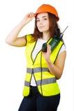 La muchacha en un chaleco de la construcción y un casco con un taladro eléctrico Imágenes de archivo libres de regalías