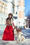 La muchacha en un chaleco de la piel y un vestido rojo que camina con el perro imagenes de archivo