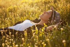 La muchacha en un dremet del sombrero entre wildflowers Imagenes de archivo