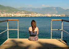 La muchacha en un embarcadero mira lejos Imagen de archivo libre de regalías