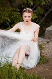 La muchacha en un estilo blanco del boho del vestido del cordón la ajusta en las rodillas El sentarse en las rocas Imagenes de archivo