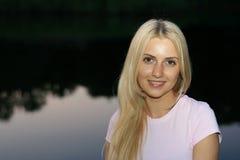 La muchacha en un fondo el río Imágenes de archivo libres de regalías