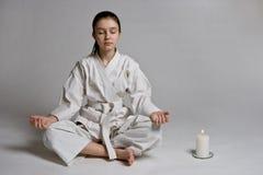 La muchacha en un kimono de los deportes meditates Foto de archivo libre de regalías
