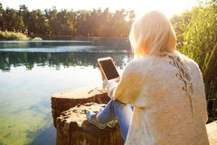 La muchacha en un parque del otoño cerca de un lago sostiene una tableta Imágenes de archivo libres de regalías