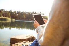 La muchacha en un parque del otoño cerca de un lago sostiene una tableta Fotos de archivo