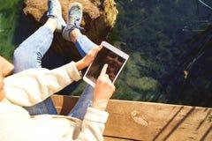 La muchacha en un parque del otoño cerca de un lago sostiene una tableta Fotografía de archivo libre de regalías