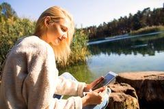 La muchacha en un parque del otoño cerca de un lago sostiene una tableta Imagen de archivo