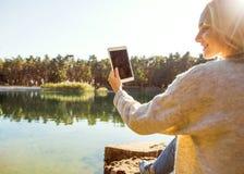 La muchacha en un parque del otoño cerca de un lago sostiene una tableta Foto de archivo