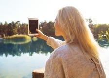 La muchacha en un parque del otoño cerca de un lago sostiene una tableta Fotografía de archivo