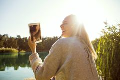 La muchacha en un parque del otoño cerca de un lago sostiene una tableta Fotos de archivo libres de regalías