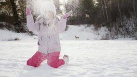 La muchacha en un parque es feliz sobre nieve que lanza para arriba metrajes