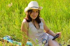 La muchacha en un prado con handheld Imágenes de archivo libres de regalías