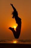 La muchacha en un salto y una puesta del sol anaranjada Foto de archivo libre de regalías