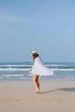 La muchacha en un sombrero camina en la playa Fotos de archivo