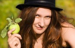 La muchacha en un sombrero con una manzana Imagen de archivo libre de regalías