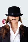 La muchacha en un sombrero con una rosa en sus dientes imágenes de archivo libres de regalías