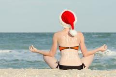 La muchacha en un sombrero de Papá Noel con un Año Nuevo de la inscripción en ella se sienta cómodamente Imagenes de archivo