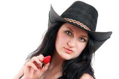 La muchacha en un sombrero de vaquero sostiene una fresa Fotografía de archivo libre de regalías