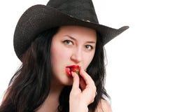 La muchacha en un sombrero de vaquero sostiene una fresa Fotos de archivo