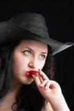 La muchacha en un sombrero de vaquero sostiene una fresa Imagen de archivo