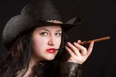 La muchacha en un sombrero de vaquero y con una boquilla Fotos de archivo libres de regalías