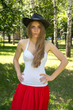 La muchacha en un sombrero de vaquero y una falda roja en verano parquean Imagen de archivo