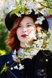 La muchacha en un sombrero goza de las flores de la primavera Imágenes de archivo libres de regalías