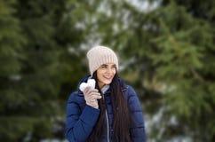 La muchacha en un sombrero hecho punto y guantes sostiene una nieve bajo la forma de h foto de archivo libre de regalías