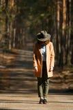La muchacha en un sombrero se coloca en la manera de árboles forestales imágenes de archivo libres de regalías