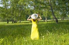 la muchacha en un sombrero y un vestido amarillo cuesta una parte posterior en la madera en el verano Fotografía de archivo