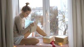 La muchacha en un suéter desempaqueta los regalos y la sentada metrajes