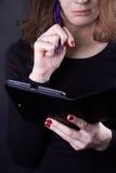 La muchacha en un suéter negro mira cuidadosamente en un cojín Fotos de archivo