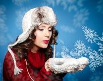 La muchacha en un suéter rojo arranca los copos de nieve en sus manos Foto de archivo