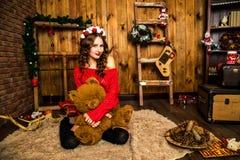 La muchacha en un suéter rojo se sienta con un oso de peluche La Navidad y nuevo Imagen de archivo