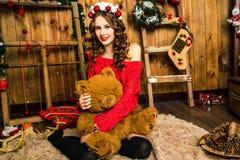 La muchacha en un suéter rojo se sienta con un oso de peluche La Navidad y nuevo Imagenes de archivo