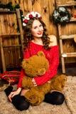 La muchacha en un suéter rojo se sienta con un oso de peluche La Navidad y nuevo Imágenes de archivo libres de regalías