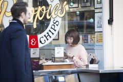 La muchacha en un suéter rosado en una tabla en un café mira en su teléfono mientras que espera la comida foto de archivo libre de regalías