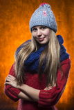 La muchacha en un suéter un casquillo y una bufanda en un fondo anaranjado Fotografía de archivo libre de regalías