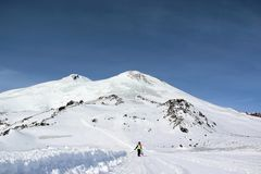 La muchacha en un traje colorido con una snowboard está en el camino de la montaña fotografía de archivo libre de regalías