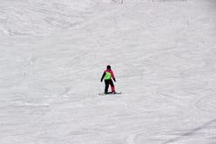 La muchacha en un traje colorido está en paseos de una snowboard con las montañas fotos de archivo