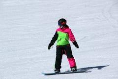 La muchacha en un traje colorido está en paseos de una snowboard con las montañas imagen de archivo libre de regalías