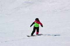 La muchacha en un traje colorido está en paseos de una snowboard con las montañas foto de archivo