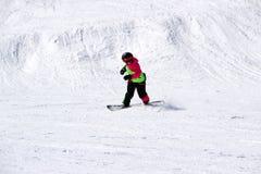 La muchacha en un traje colorido está en paseos de una snowboard con las montañas foto de archivo libre de regalías