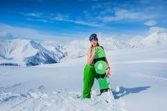 La muchacha en un traje de baño abraza un tablero de la snowboard Imágenes de archivo libres de regalías